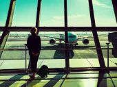 Back View Of Young Tourist Woman Looking Out Of Window In Airport Lounge. poster