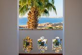 Balcony With A View Of The Blue Sea. Tall Palm Tree Next To The Bolcony At The Sea Resort. View Of A poster