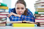 stock photo of pouting  - Portrait of a frustrated student being surrounded with piles of books - JPG