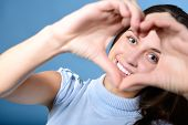 stock photo of love making  - portrait of attractive happy smiling teen making heart of her hands - JPG
