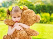 Little cute sad girl holding in hands brown teddy bear, upset child spending time outdoors in spring