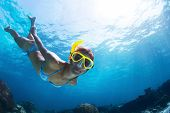 stock photo of bottom  - Underwater shoot of a young lady snorkeling and doing skin diving in a tropical sea - JPG