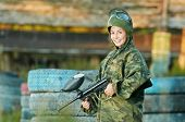 stock photo of paintball  - Happy paintball sport player girl in protective camouflage uniform and mask with marker gun outdoors - JPG