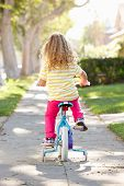 stock photo of bike path  - Girl Learning To Ride Bike On Path - JPG