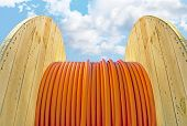 pic of drums  - Wooden cable drum with orange cable on blue sky - JPG