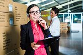 stock photo of labourer  - Young woman in a suit with headset in a warehouse - JPG