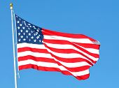 stock photo of flag pole  - The american flag in the wind against the blue sky - JPG