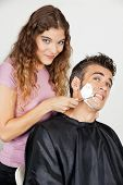 Scared mature man being shaved by female barber at salon