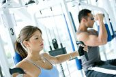 picture of gym workout  - man and woman doing exercises in the gym - JPG