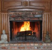 stock photo of cozy hearth  - A fireplace and mantel inside a cozy family room - JPG