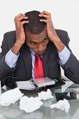 pic of outrageous  - Frustrated young Afro businessman with head in hands at desk against white background - JPG