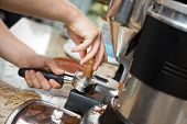 Cropped image of barista with portafilter and tamper leveling coffee