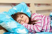 Beautiful Little Girl Sleep In Bed Under A Blue Blanket
