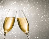 image of flute  - champagne flutes with golden bubbles make cheers on silver light bokeh background with space for text - JPG