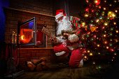 picture of nicholas  - Santa Claus keep the fire in the stove near Christmas tree - JPG