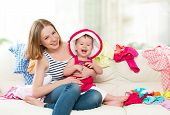 foto of dowry  - Happy Mother and baby girl with clothes ready for traveling on vacation - JPG