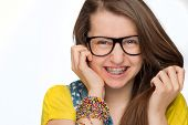 pic of geek  - Cheerful girl with braces wearing geek glasses on white background - JPG