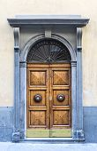 pic of fortified wall  - An old wooden double door with ornate handles surrounded by a carved stone decorative frame in a cement rendered wall - JPG