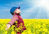 stock photo of rape  - girl in a yellow field of rape - JPG