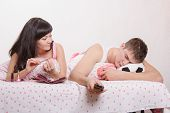 image of sarcasm  - Young girl and a guy in bed. Beautiful girl has a manicure man watching soccer on TV