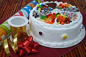 picture of fancy cake  - A birthday cake topped with assorted candy next to wrapping paper - JPG