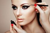 stock photo of human face  - Makeup artist applies eye shadow - JPG