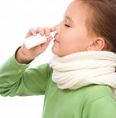 foto of snot  - Cute girl spraying her nose with nasal spray isolated over white - JPG