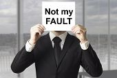 stock photo of fail job  - businessman in black suit hiding face behind sign not my fault failed - JPG