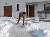 image of snow shovel  - Man clearing path to his house of snow with shovel after heavy snowing - JPG