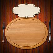 stock photo of oval  - Wooden oval cutting board with empty label and silver cutlery fork and knife on wooden table - JPG