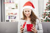 stock photo of sad christmas  - young attractive girl is sad or unhappy about christmas gift - JPG