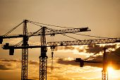 foto of construction crane  - Color picture of some cranes on a construction site as dusk - JPG