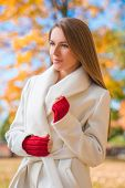 foto of overcoats  - Elegant confident young woman in a stylish white overcoat and red mittens standing - JPG