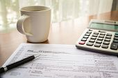 pic of income tax  - Form 1040A U.S. Individual income tax return place on table with a cup of coffee calculator and pen ** Note: Soft Focus at 100%, best at smaller sizes - JPG