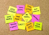 image of quit  - Group of New year Resolutions Post Notes on pink yellow orange and green on cork board written with message of diet join gym find love quit smoking and be happy - JPG