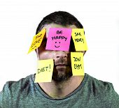 stock photo of overwhelming  - young man overwhelmed and overworked in stress with face full of sticky notes stuck covering him with reminders and resolutions isolated on white background - JPG