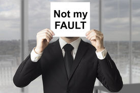 image of fail job  - businessman in black suit hiding face behind sign not my fault failed - JPG
