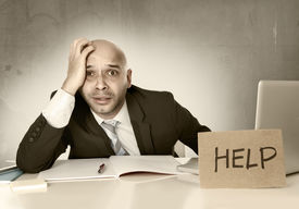 stock photo of bald headed  - overworked unhappy bald Hispanic businessman in stress wearing suit and tie at office holding help sign working on desk with computer laptop looking frustrated and anxious - JPG