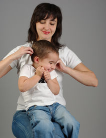 stock photo of titillation  - Mother titillates her son on gray background - JPG