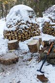 image of ax  - Firewood stacked in a woodpile and covered with snow - JPG