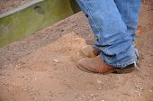 pic of work boots  - closeup of a person wearing brown leather cowboy boots and jeans standing in the dirt - JPG
