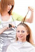 stock photo of hair dye  - Young beautiful hairdresser coloring hair with hair color - JPG