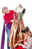 stock photo of dress mannequin  - two happy seamstresses working on a dress on a mannequin isolated over a white background