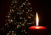 picture of candle flame  - Flame coming from a red candle near a Christmas tree - JPG