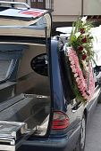 stock photo of hearse  - black hearse with a wreath of flowers ready to go to funeral - JPG