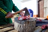 stock photo of slaughter  - Cutting the meat with axe over stump tree - JPG