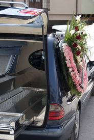foto of funeral  - black hearse with a wreath of flowers ready to go to funeral - JPG