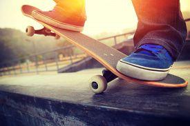foto of skateboard  - young skateboarder legs skateboarding at skate park - JPG