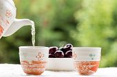 stock photo of teapot  - fresh healthy hot tea in a teapot and cup whit cherries - JPG
