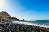 foto of atlantic ocean  - Wild stone beach on coast or shore of the Atlantic ocean with waves and blue sky and skyline or horizon in Tenerife Canary island Spain - JPG